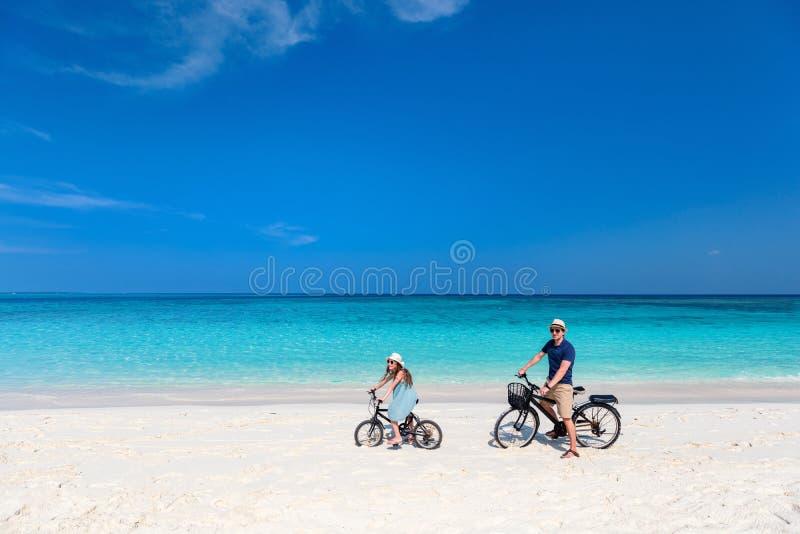 Fader- och dotterridningen cyklar på den tropiska stranden royaltyfri bild
