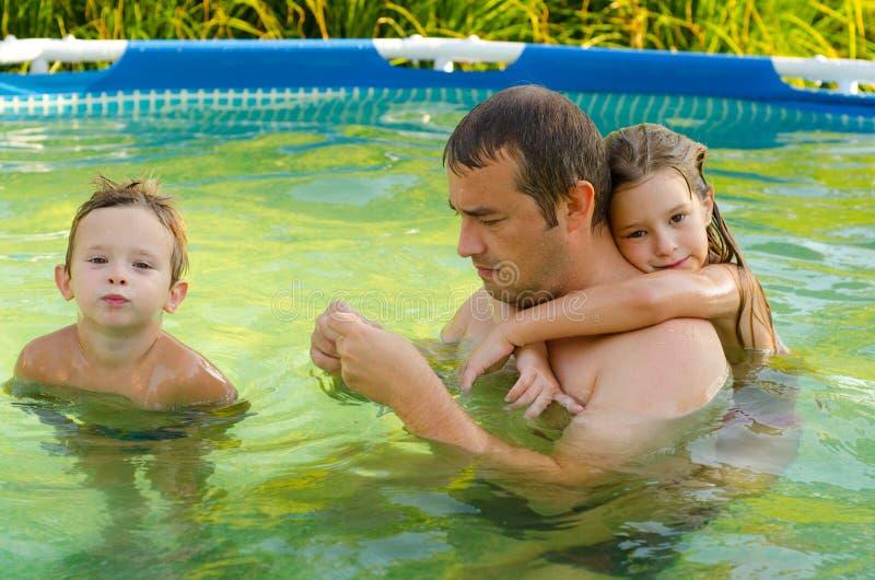 Fader och hans barn i simbassängen royaltyfri bild