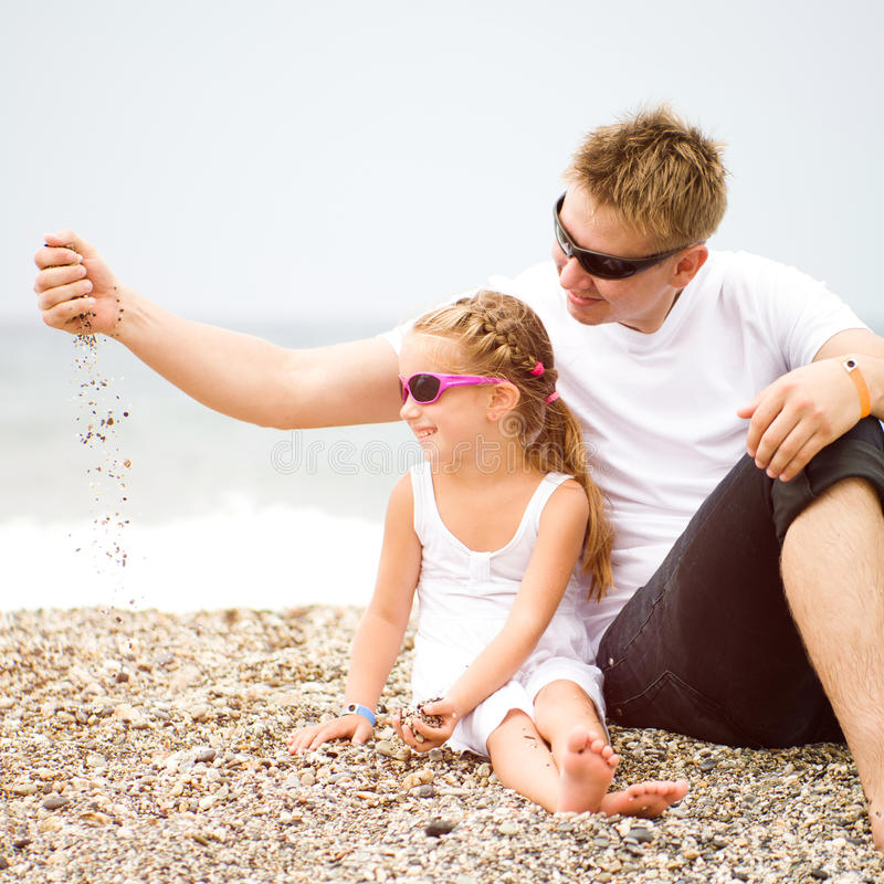 Fader och hans dotter på stranden fotografering för bildbyråer