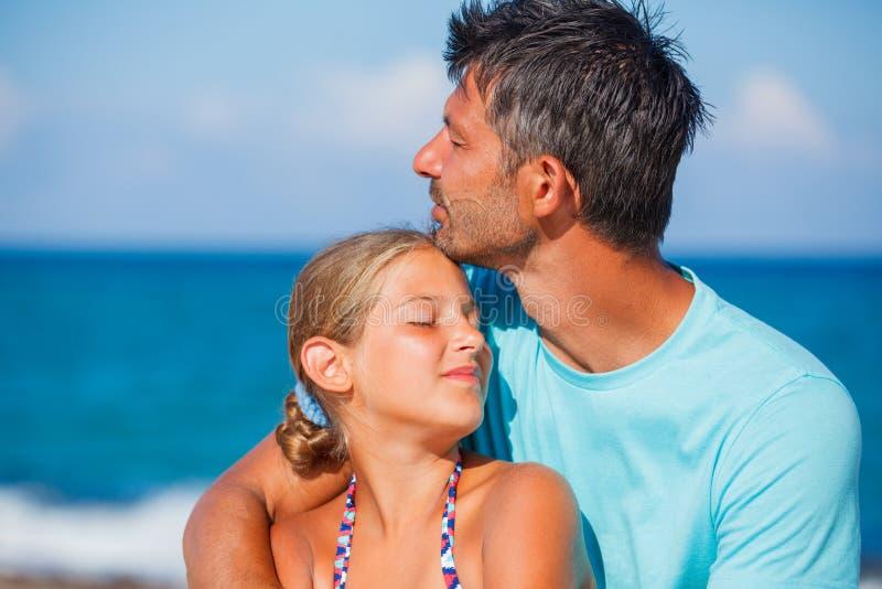 Fader och hans dotter på stranden arkivbild