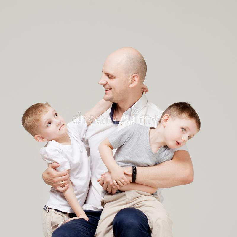 Fader och hans två söner, den unga mannen som lyfter barn, begreppsståenden royaltyfri bild