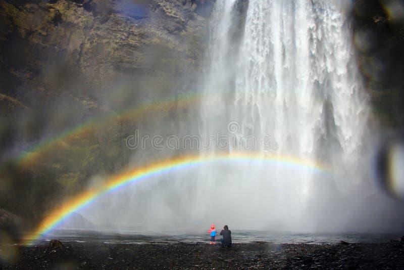 Fader och liten dotter på den Skogafoss vattenfallet under regnbågen, Island arkivfoto