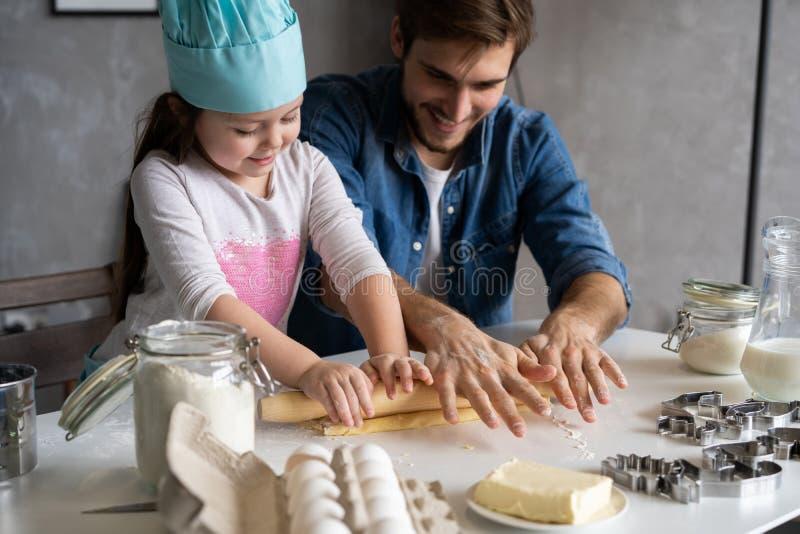 Fader och liten dotter som bakar bakelser Familj som har gyckel i kök och får klar för ett parti royaltyfri foto