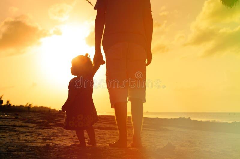Fader och liten dotter som går på stranden på arkivfoto