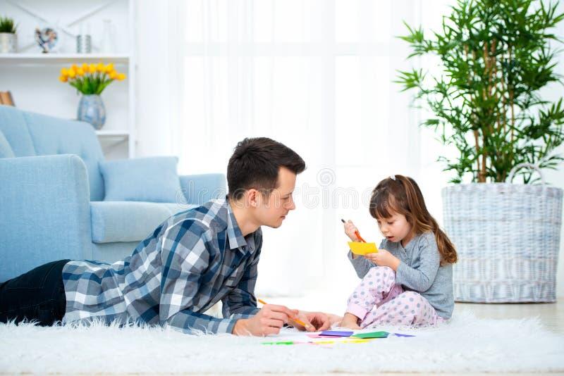 Fader och liten dotter som har kvalitets- familjtid tillsammans hemma farsa med flickan som ligger på varm golvteckning med färgr fotografering för bildbyråer