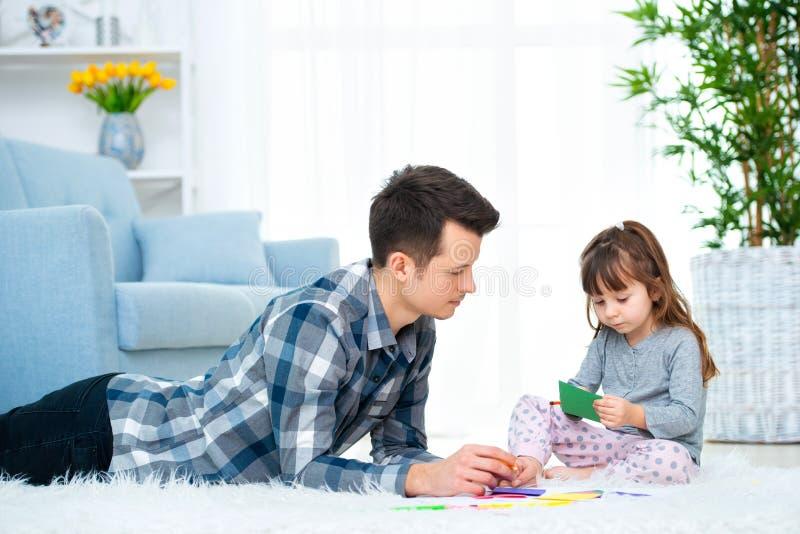 Fader och liten dotter som har kvalitets- familjtid tillsammans hemma farsa med flickan som ligger på varm golvteckning med färgr arkivfoto