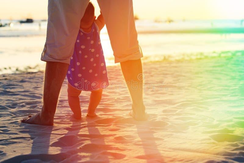 Fader och liten dotter som lär att gå på stranden royaltyfria foton