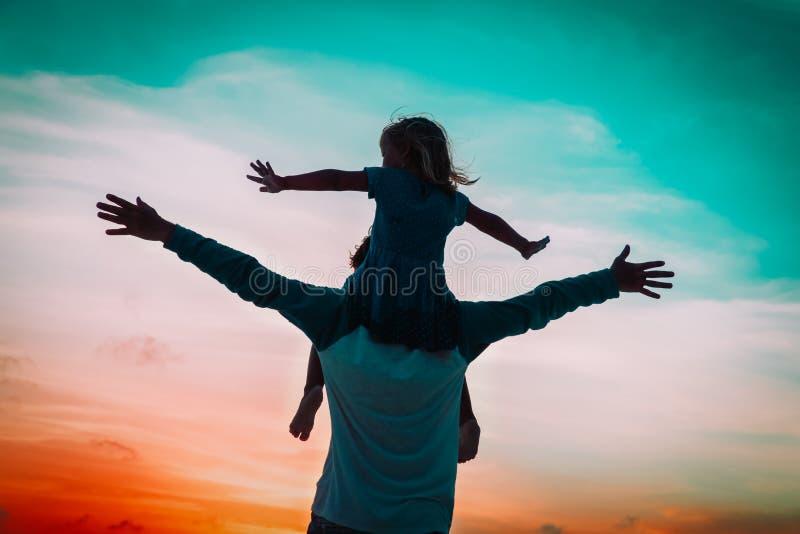 Fader och liten dotterlek på solnedgånghimmel royaltyfri foto
