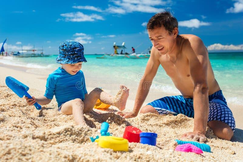 Fader och liten son som spelar med sand arkivbilder