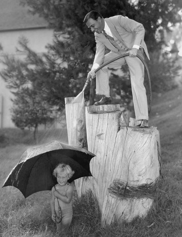 Fader och litet barn som spelar med slangyttersidan (alla visade personer inte är längre uppehälle, och inget gods finns Leverant arkivbild