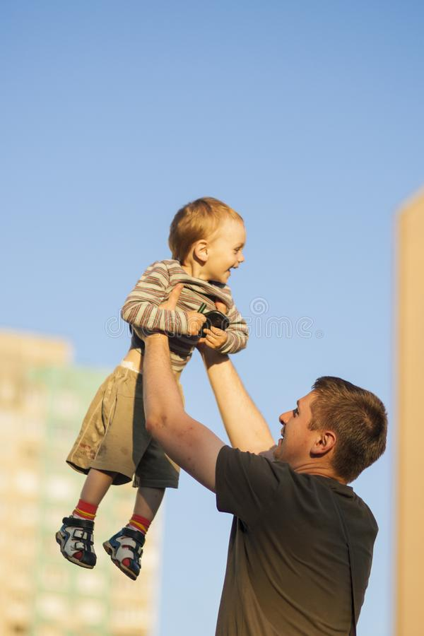 Fader och lycklig son som tillsammans utomhus spelar Farsa som kastar sonen upp mot blå himmel royaltyfri bild