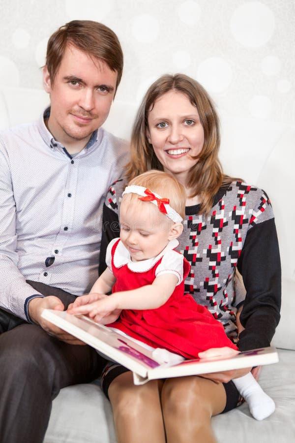 Fader- och modersammanträde med behandla som ett barn flickan som ser i bok royaltyfri foto