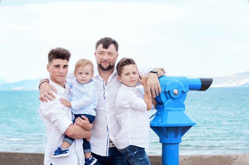 Fader och söner på havet Familj på visningplattformen nära myntet royaltyfria bilder
