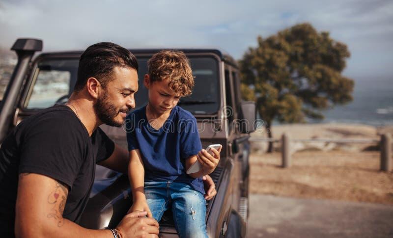 Fader och son framme av bilen genom att använda den smarta telefonen arkivfoton