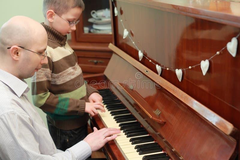 Fader och son i exponeringsglas som leker pianot royaltyfri bild