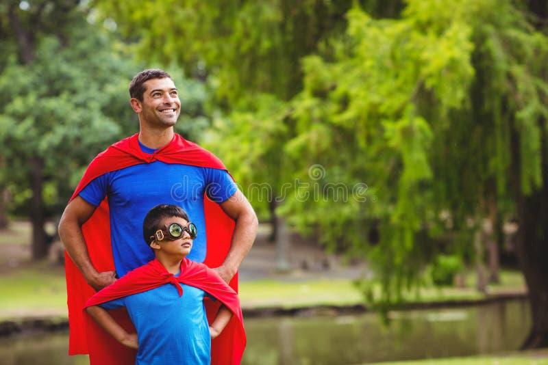 Fader och son i superherodräkt royaltyfria foton