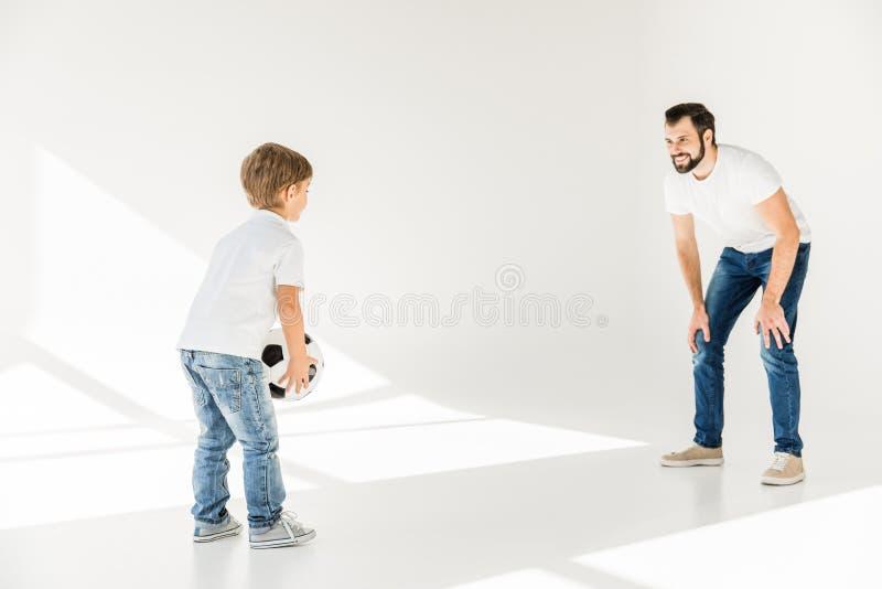 Fader och son med fotbollbollen royaltyfria foton