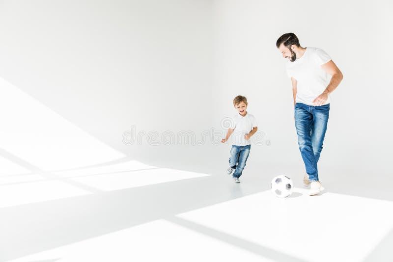 Fader och son med fotbollbollen fotografering för bildbyråer