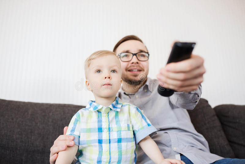 Fader och son med hållande ögonen på tv för fjärrkontroll hemma arkivbild