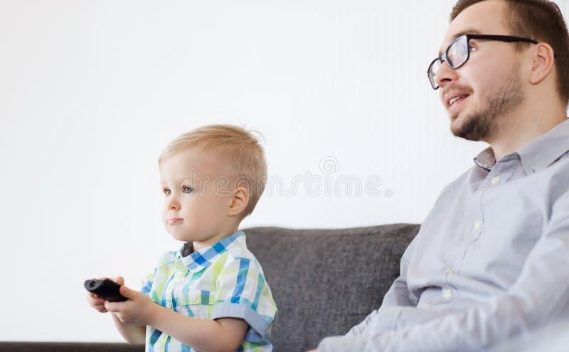 Fader och son med hållande ögonen på tv för fjärrkontroll hemma royaltyfri bild