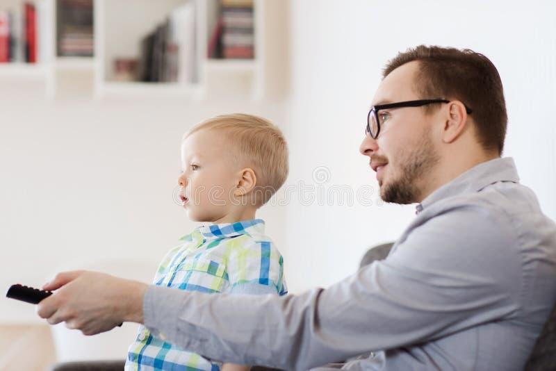 Fader och son med hållande ögonen på tv för fjärrkontroll hemma royaltyfria bilder