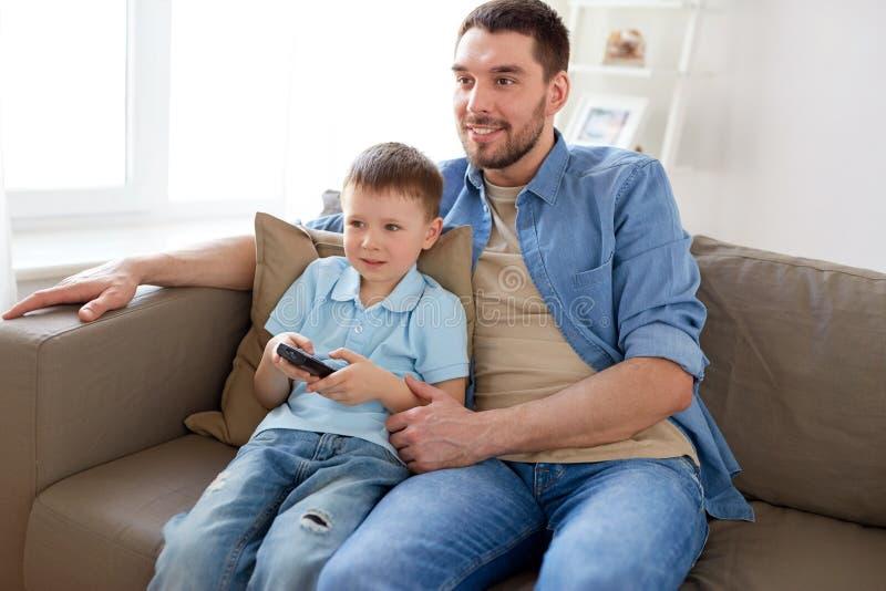 Fader och son med hållande ögonen på tv för fjärrkontroll hemma fotografering för bildbyråer