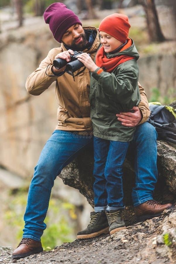 Fader och son med kikare arkivbild