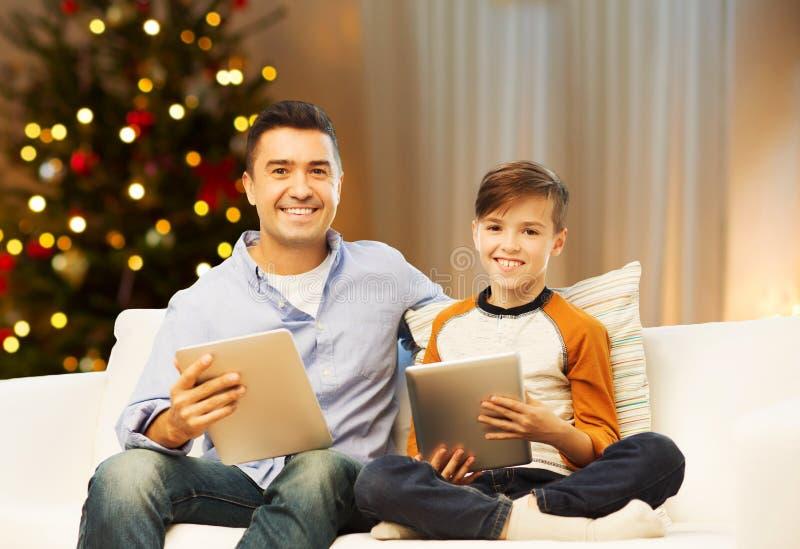 Fader och son med minnestavladatorer på jul arkivbild
