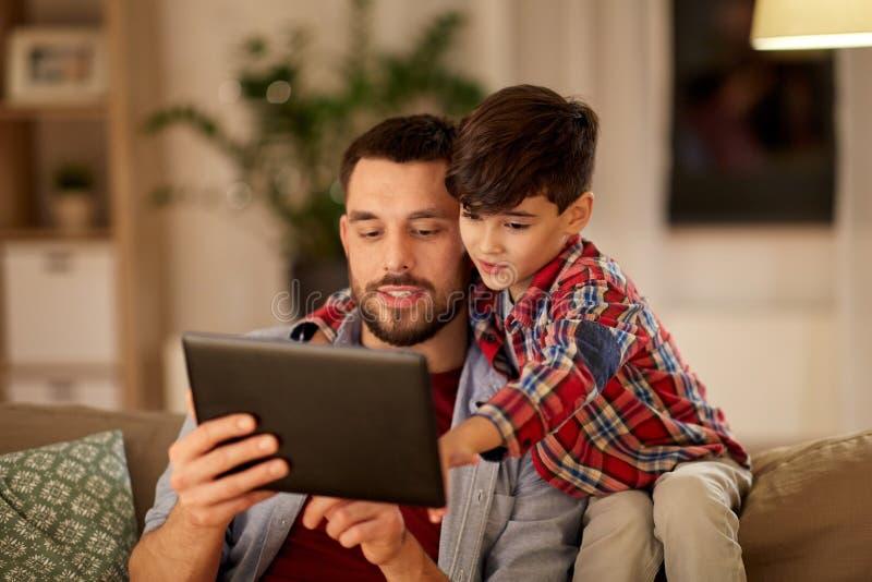 Fader och son med minnestavlaPC:n som hemma spelar arkivfoto