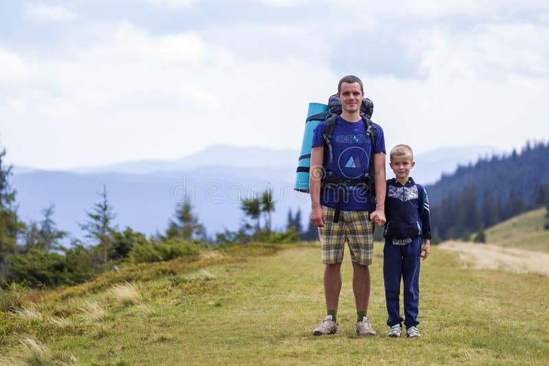 Fader och son med ryggsäckar som går samman i scengröna sommarberg Pappa och barn som njuter av landskapsberget royaltyfria bilder
