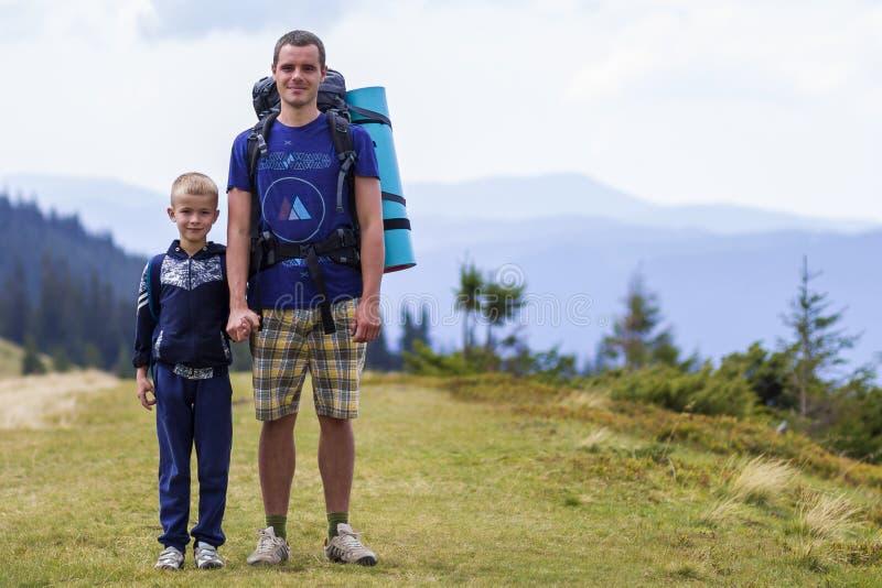 Fader och son med ryggsäckar som går samman i scengröna sommarberg Pappa och barn som njuter av landskapsberget arkivfoton