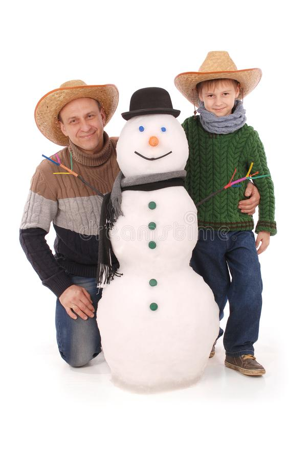 Fader och son med snögubben med halsduken och hatten royaltyfri foto