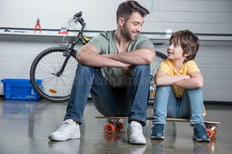 Fader och son med vikta armar som sitter på skateboarden och ser de royaltyfri fotografi