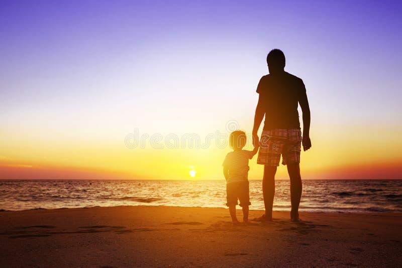 Fader och son på solnedgångstranden arkivfoton