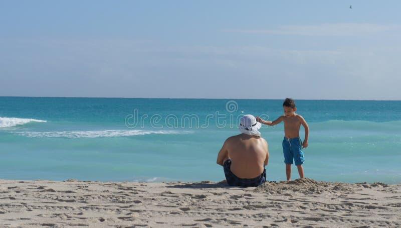 Fader och son på stranden royaltyfria foton
