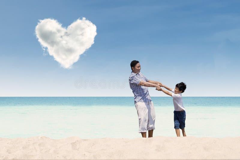 Fader och son på stranden arkivbilder