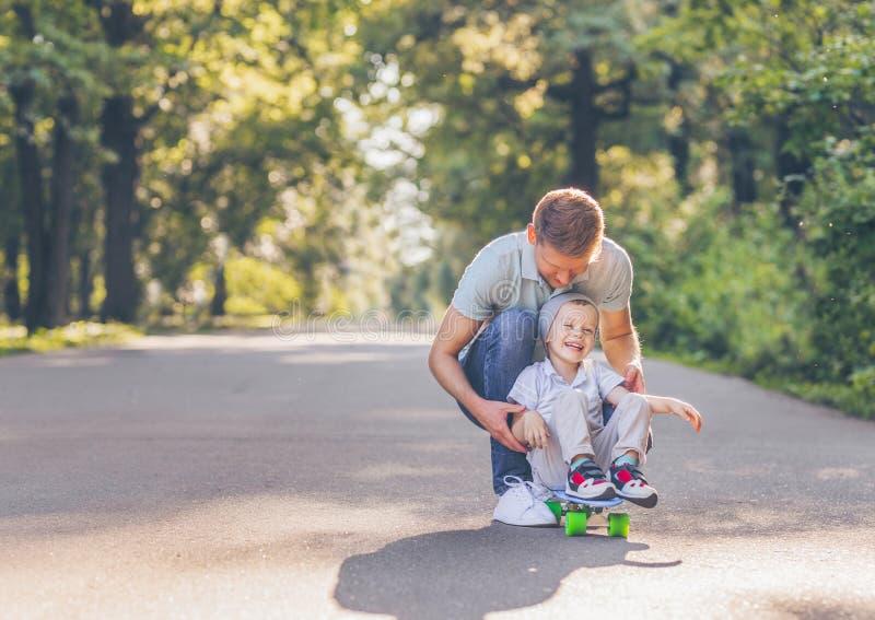 Fader och son som åker skridskor i sommar royaltyfri bild