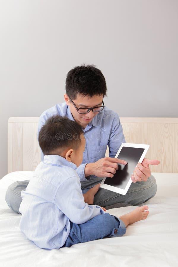 Fader och son som använder tabletPC arkivbilder