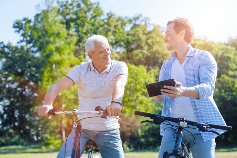 Fader och son som använder touchpaden, medan rida deras cyklar royaltyfri fotografi