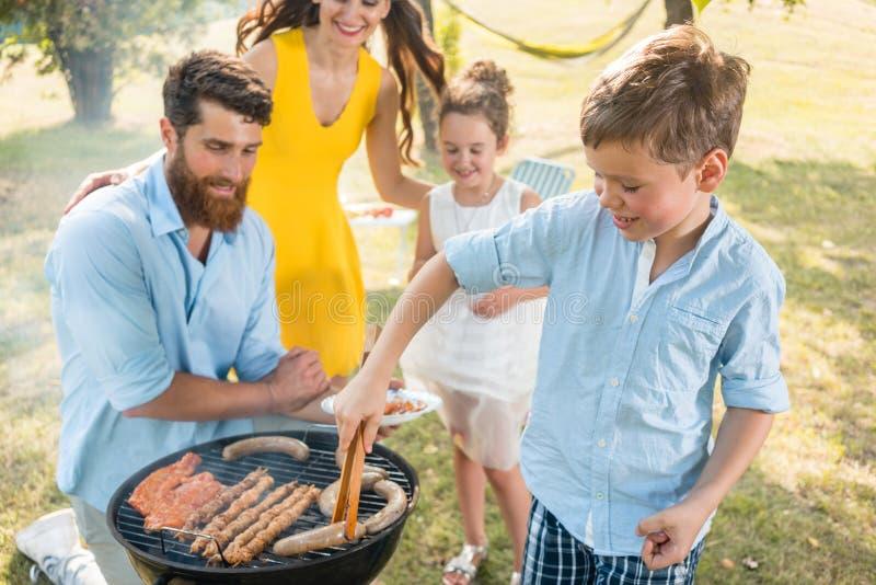 Fader och son som förbereder kött på kolgrillfestgaller under picknick royaltyfria foton