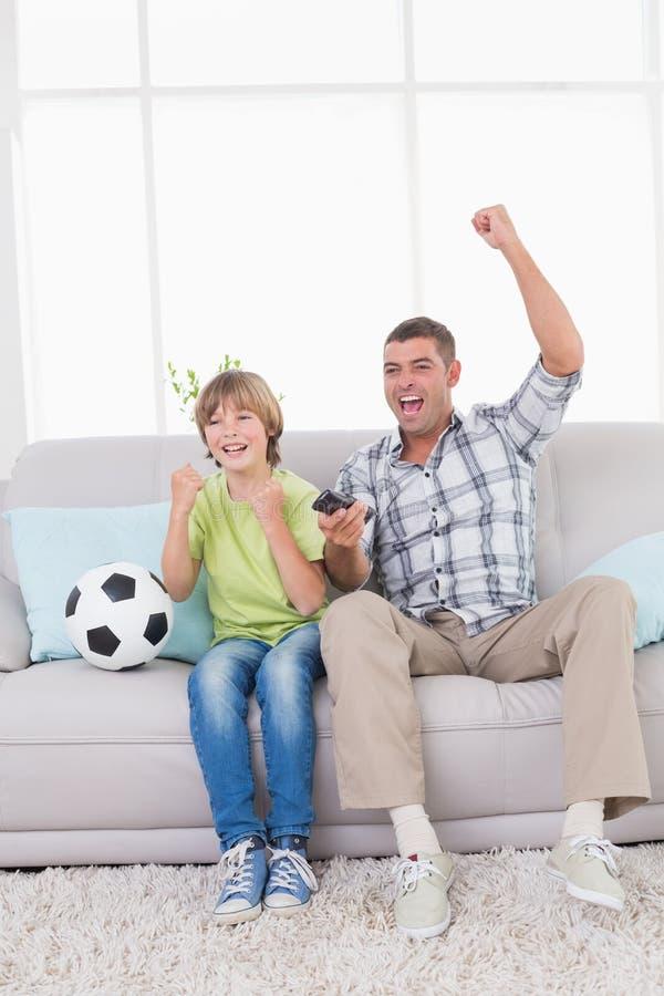 Fader och son som firar framgång, medan hålla ögonen på fotbollsmatchen royaltyfria foton