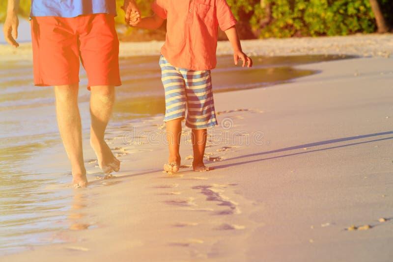 Fader och son som går på stranden som lämnar fotspår arkivfoton
