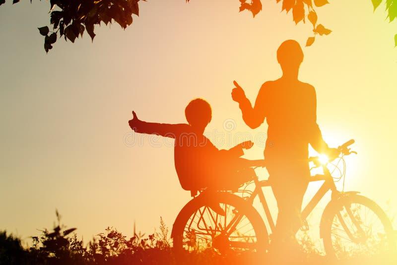 Fader och son som har den roliga ridningcykeln på solnedgången arkivfoton