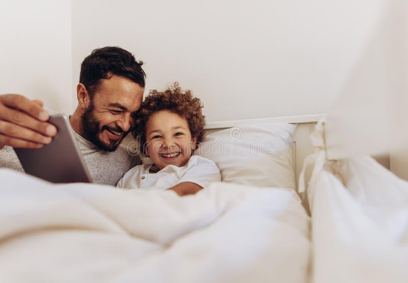 Fader och son som har gyckel hemma fotografering för bildbyråer
