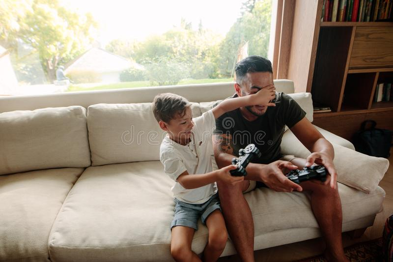 Fader och son som har gyckel som hemma spelar videospel royaltyfri bild