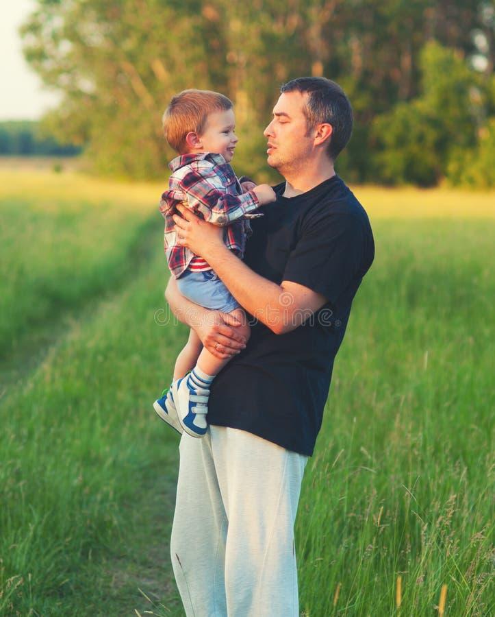 Fader och son som har gyckel i naturen på solig vårdag arkivfoto