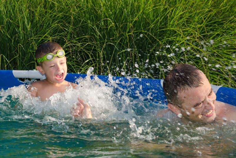 Fader och son som har gyckel i simbassängen royaltyfri foto