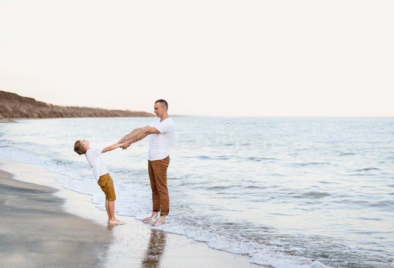 Fader och son som har gyckel på semestern för familj för havskust kamratskap fotografering för bildbyråer