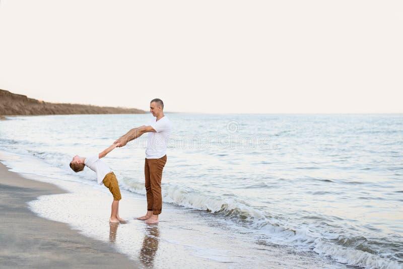 Fader och son som har gyckel på semestern för familj för havskust kamratskap arkivbild