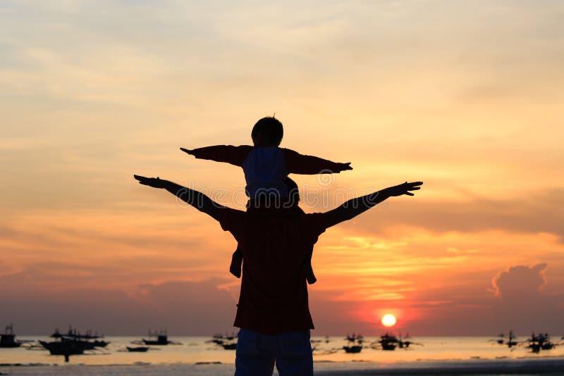 Fader och son som har gyckel på solnedgångstranden royaltyfri bild